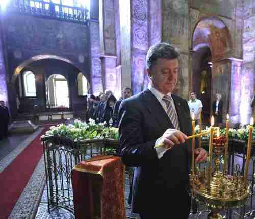 Petro Poroshenko lights a candle in St. Sophia Cathedral after his inauguration in Kiev on Saturday (AP)