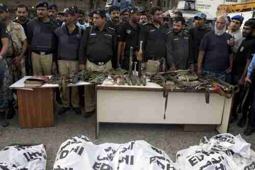 Police display confiscated suicide vests and heavy weapons brought in by the terrorists.  In the foreground are the dead bodies of the terrorists in white sacks (AP)