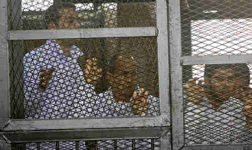Caged Al-Jazeera journalists in court on Monday (AP)