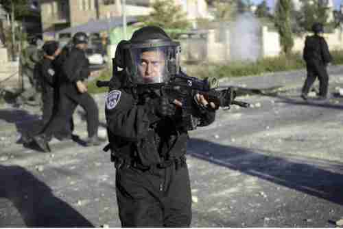 Israeli policeman aims his weapon during clashes with Palestinians on Thursday (AP)