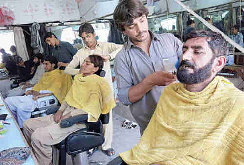 Taliban militants get their hair and beards trimmed so they won't look like killers (AFP)