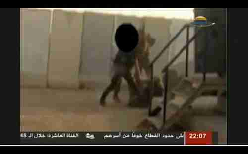 Screen grab from Hamas video showing Hamas fighters kicking Israeli soldier
