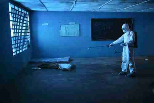 A health worker disinfects a corpse in an Ebola isolation ward, once a primary school, in Monrovia (National Geographic)