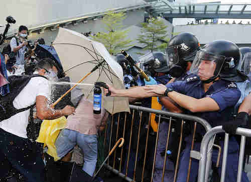 Riot police use pepper spray in Hong Kong on Sunday (Slate)