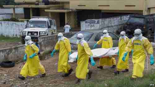 Health care workers in Liberia carry the body of an Ebola victim (EPA)