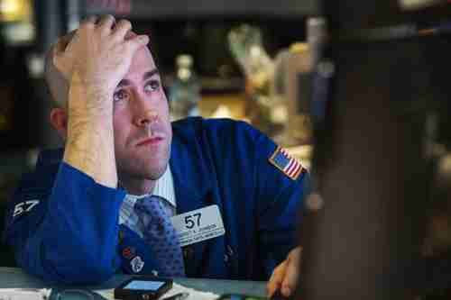 A trader watches the screen at his terminal on the floor of the NY Stock Exchange on Wednesday (Reuters)