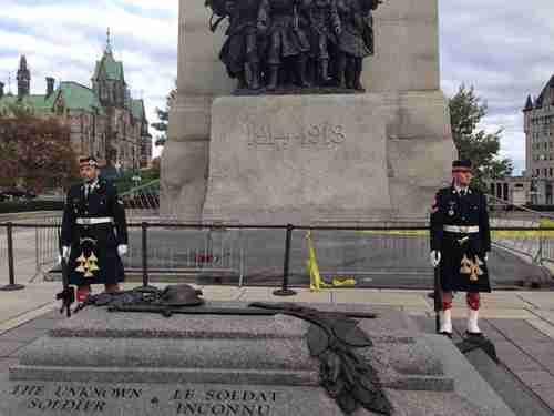 A Twitter user took this photo moments before the shooting.  He tweeted: 'Ok so we were on a tour at that war monument in Ottawa a few minutes ago, a few seconds later there was a shooting.' Is one of these guards the soldier who was killed? (@Evanem/Toronto Star)