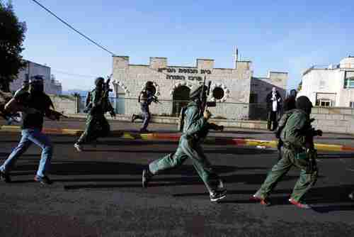 Israeli security forces run in front of the synagogue that was attacked on Tuesday