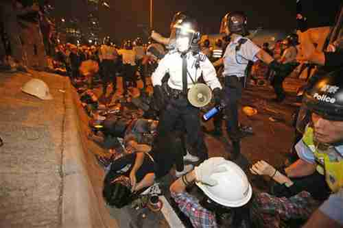 Protesters clash with police officers on the main road outside government headquarters in Hong Kong on Sunday (AP)