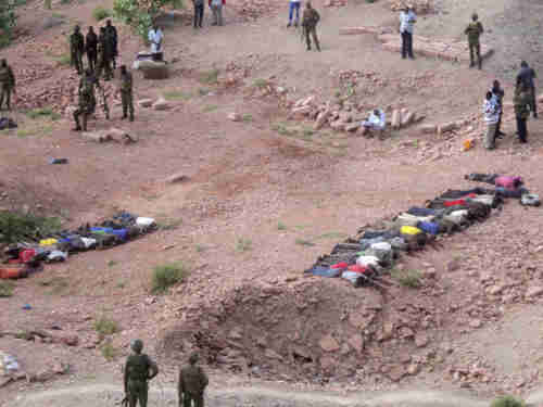 Soldiers of Kenyan Defense Forces look over the bodies of some 36 Kenyans killed by al-Shabaab on Tuesday (AP)