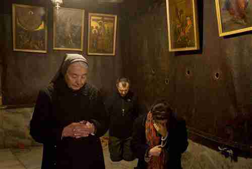 Christian pilgrims pray inside the Grotto of the Church of the Nativity, thought to be the birthplace of Jesus Christ, in Bethlehem on Wednesday. (AP)