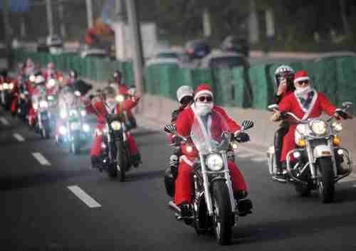 Owners of Harley-Davidson motorcycles wearing Santa Claus costumes ride along a street to give presents to elders at a nursing home during a promotional event celebrating Christmas in Guangzhou, Guangdong province on Dec. 24, 2014 (Reuters)