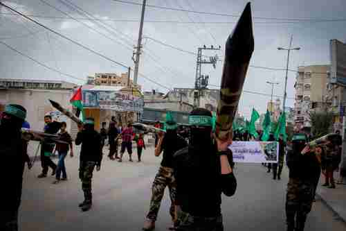 Masked Hamas members carry a model of a rocket in a Gaza rally in December (Flash90)