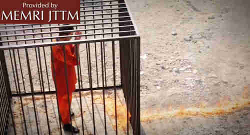 Muath al-Kaseasbeh, drenched in gasoline, watches as the flames approach his cage to burn him alive, in screen grab from ISIS video.  (Memri)