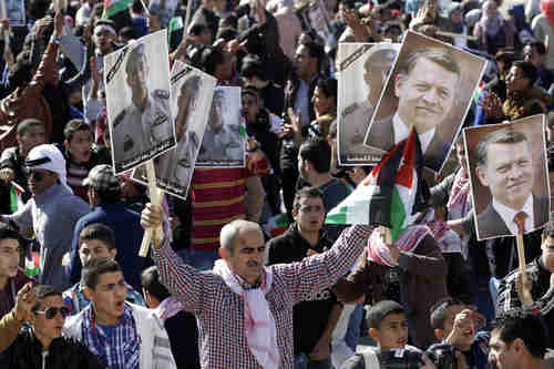 Jordanians chant slogans to show support for government action against ISIS, carrying posters of the slain pilot and of King Abdullah II (AP)