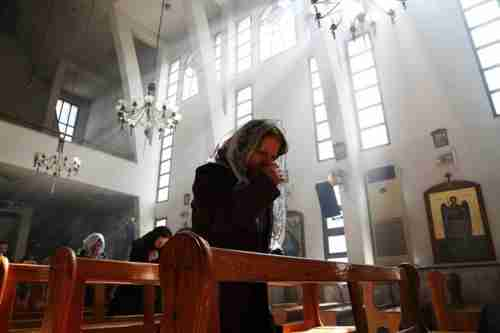 An Assyrian woman in church prays for Christians abducted by ISIS (Reuters)