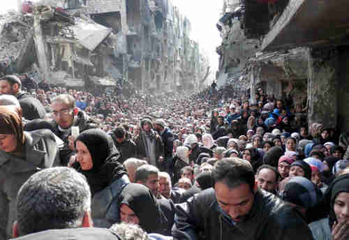Yarmouk refugee camp, 31-Jan-2014, showing residents queuing up to receive food supplies (AP)