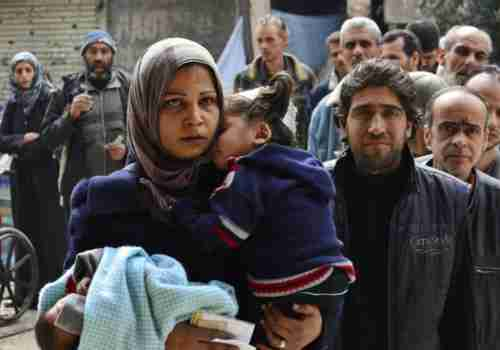 Yarmouk residents queue up to receive humanitarian aid (Reuters)