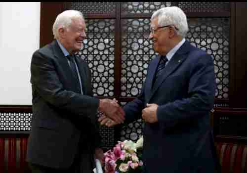 Jimmy Carter shakes hands with Palestinian president Mahmoud Abbas in Ramallah, the West Bank, on Saturday (Reuters)