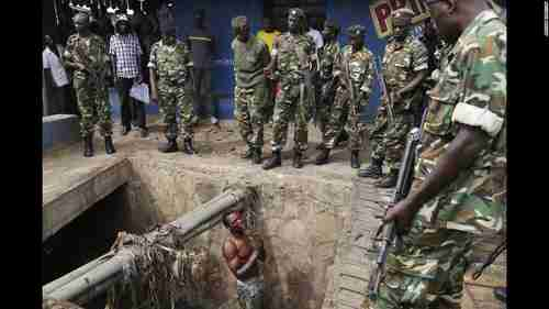 A Hutu youth who escaped a Tutsi mob by hiding in the sewer on Thursday begs for mercy from Burundi soldiers (CNN)