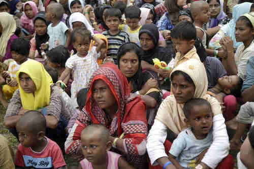 Ethnic Rohingya women and children gather to receive a meal in Indonesia on Saturday (AP)