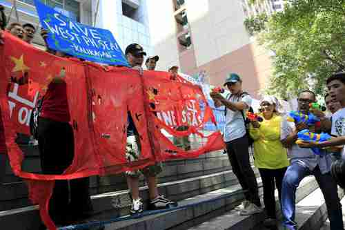 Anti-Chinese environment activists in Manila protest in front of the Chinese embassy, shooting Chinese flags with water guns (Reuters)