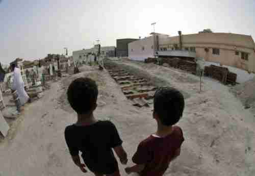 Two Shia Saudi boys stand at the graves of 21 people killed in the May 22 attack on a Shia mosque (EPA)