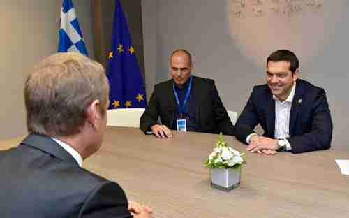 The wily Greek finance minister Yanis Varoufakis watches as Greek PM Alexis Tsipras grins broadly at something amusing said by European Commission president Donald Tusk (Kathimerini)