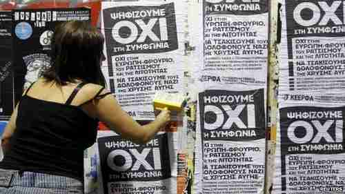 A woman in Athens puts up referendum campaign posters.  'OXI' means 'NO' in Greek.  (Reuters)