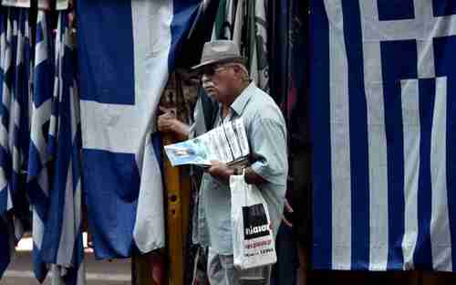 An old man carrying newspapers stands in front of a row of Greek flags in Athens (Kathimerini)