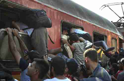 Migrants in Gevgelija Macedonia railway station desperately try to get onto train to Serbia (EPA)