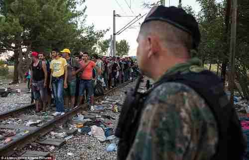 Hundreds of migrants stand in line on a railway track as uniformed police watch on (Athena Pictures)