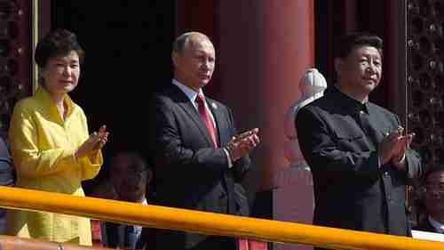 South Korea's president Park (L) holds a place of honor at China's victory parade, next to Vladimir Putin and Xi Jinping (R) on the reviewing stand (AP)