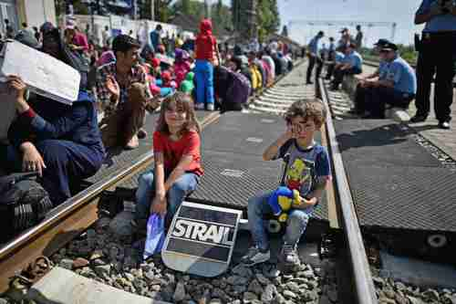 Two children sit on the tracks as hundreds of migrants wait for the train in Tovarnik, Croatia, just across the border from Serbia (Getty)