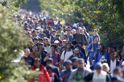 Migrants walk towards the Austrian border from Hungary on Wednesday.  At least 7,000 people crossed from Hungary into Austria on Wednesday alone.  (Reuters)