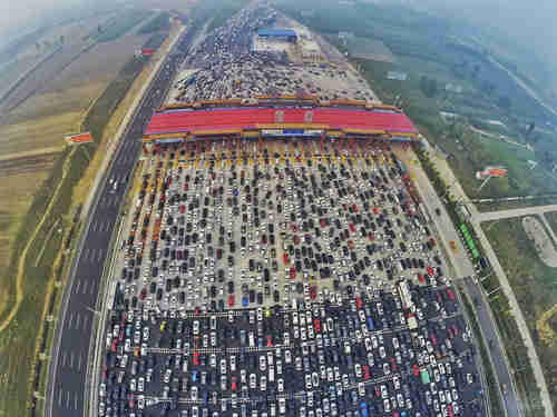 Vehicles stuck in week-long traffic jam on 30-lane highway as they approach a toll booth near Beijing.  (Reuters)