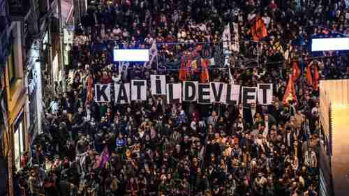 Anti-government protesters carry placards reading, 'The Murderous State'
