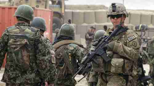 Afghan soldiers, left, walk past a U.S. Army soldier in a military base in 2012 (AP)