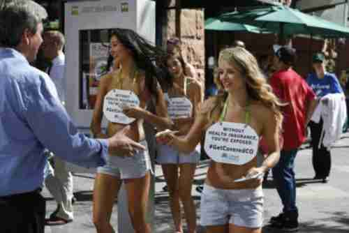 An October 2013 promotional campaign for Colorado HealthOP features hot, scantily clad girls carrying signs saying, 'Without health insurance, you're exposed.' (AP)