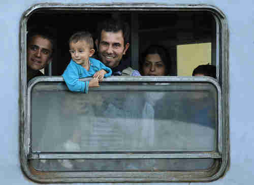 Members of a migrant family look out from a train window at a station in Cakovec, Croatia (Reuters)