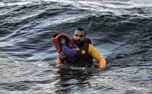 Refugee father in Aegean Sea scrambles for shore with his son.  More than 100 children have drowned in the Aegean over the last two months.  (Kathimerini)