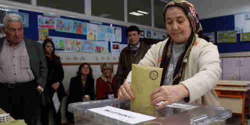 A Turkish woman casts her vote on Sunday in Ankara (AP)