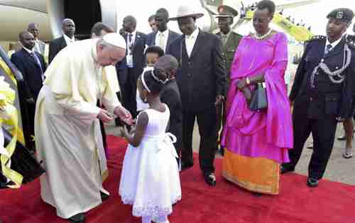 Pope Francis welcomed by Uganda's president Yoweri Museveni (at right with hat), in Kampala on Friday (AP)