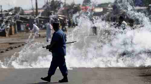 A policeman walks away after throwing a tear gas canister at protesters in Bujumbura (Reuters)