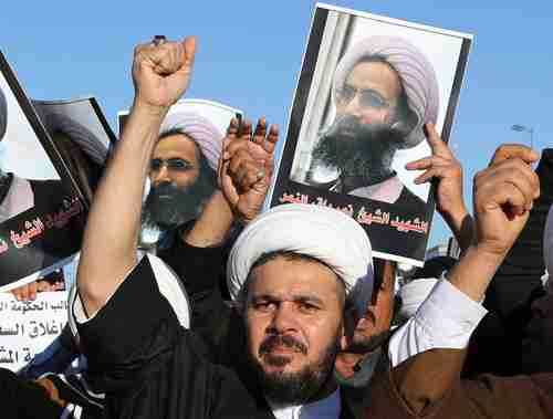 Shia protesters against Saudi Arabia holding posters showing Nimr al-Nimr in Najaf, Iraq, 100 miles south of Baghdad (AP)