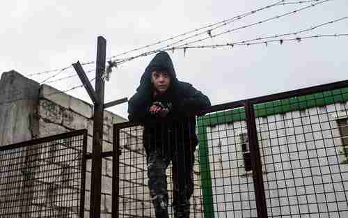 A boy on a fence watches thousands of Syrians massed on the border with Turkey in the cold and rain (AFP)