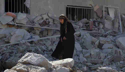 A woman makes her way through the rubble of damaged buildings after Syrian government airstrikes on Friday (Reuters)