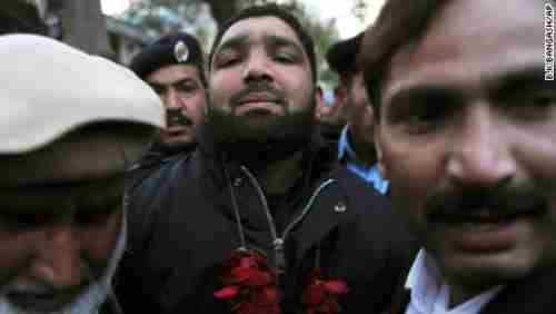 Salman Taseer's murderer, Mumtaz Qadri, arrives in court in 2011, where he's showered with rose petals (AP)