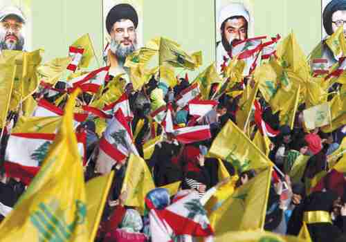 Hezbollah supporters in south Lebanon carry Hezbollah and Lebanese flags (Reuters)