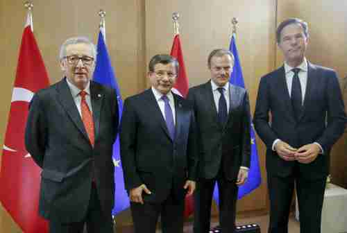 Friday in Brussels: The three EU officials look grim.  The only one smiling is the Turkey's prime minister Ahmet Davutoglu, second from the left.  (AFP)
